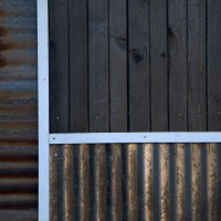 Charred Wood Siding Next To Recycled Corrugated Steel Siding.
