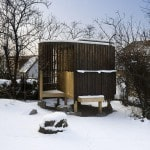 A charred wood teahouse covered in snow in Prague